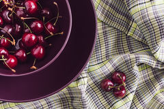 Bunch ripe cherry in purple plate on plaid background. Stock Photography