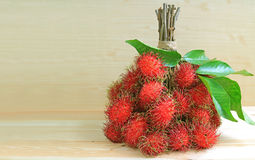 Bunch of Ripe Fresh Rambutan Fruits on Wooden Table, with Free Space for Text Royalty Free Stock Photography