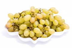 Bunch of ripe grapes. Bunch of ripe yellow grapes on a branch on plate Isolated on white Stock Images