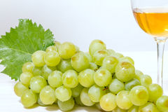 Bunch of ripe muscat grapes. And wine glasses with white wine Stock Images