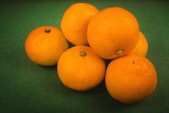 a bunch of ripe tangerines on a green background, Christmas background, new year royalty free stock image