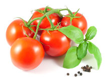 Bunch of ripe tomatoes with basil leaves and black pepper Stock Image