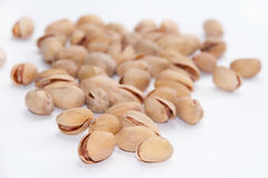 A bunch of roasted pistachios on a white background Royalty Free Stock Photography