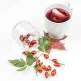 Bunch of rose hips spreaded on white background with rose hip tea Stock Images
