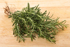 Bunch of rosemary on an old wooden chopping board Royalty Free Stock Photos
