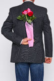 Bunch of roses behind a mans back. Royalty Free Stock Photo