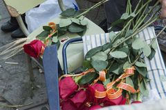 Bunch or roses with Catalan flag ribbons. A bunch of red roses with Catalan flag ribbons rest  on the chair of a florist stall ready to be sold during Sant Jordi Royalty Free Stock Images