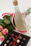 Bunch of roses, champagne bottle, wine glasses and assorted chocolate box Stock Photo