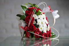 Bunch of roses and chrysanthemums. Beautiful bunch of fresh red roses white chrysanthemums decorated with green leaves bows lies sidelong on glass table on Stock Photo