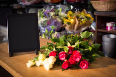 Bunch of roses and digital tablet on the wooden table Royalty Free Stock Photos
