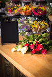 Bunch of roses and digital tablet on the wooden table Stock Image