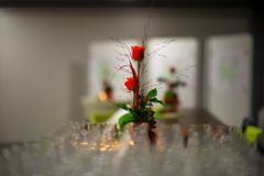 Bunch of roses and several rows of many empty drinking glasses in the restaurant stock images