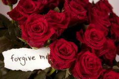 A bunch of roses in vase with note - forgive me. A bunch of roses in glass vase with note - forgive me Royalty Free Stock Photo
