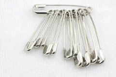 Bunch of safety pins on fabric Stock Images