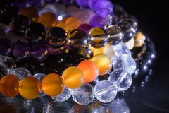 Bunch of semiprecious gemstone bracelets  on black background - cornelian, amethyst, quartz Royalty Free Stock Photography