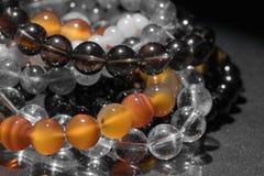 Bunch of semiprecious gemstone bracelets  on black background - cornelian, amethyst, quartz Stock Image