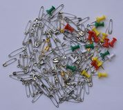 Bunch of shiny silver and gold color safety pins along with colorful push pins Stock Photo