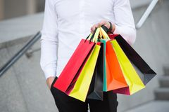 Bunch of shopping bags in male hands outdoor, close up. Shopping tips. Successful shopping expedition. What a waste. Buy. With list to not overspend and waste Stock Photos