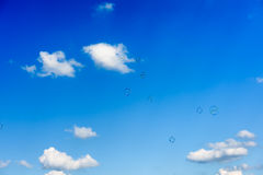 A bunch of soap bubbles flying up into the dark blue sky Royalty Free Stock Images