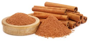 Bunch of some fresh aromatic cinnamon with powder spice. Over white background Royalty Free Stock Image