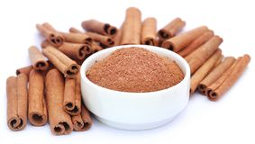 Bunch of some fresh aromatic cinnamon with powder spice. Over white background royalty free stock photo