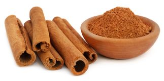 Bunch of some fresh aromatic cinnamon with powder spice. Over white background Stock Photo