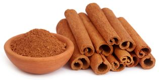 Bunch of some fresh aromatic cinnamon with powder spice. In a pottery over white background stock image