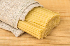 Bunch of spaghetti in burlap bag on table Royalty Free Stock Images