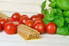 Bunch of spaghetti, cherry tomatoes and fresh basil Royalty Free Stock Photos