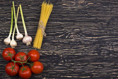 Bunch of spaghetti pasta with fresh tomatoes and garlic. Bunch of spaghetti pasta with fresh tomatoes and garlic on wooden table Stock Photography