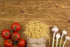 Bunch of spaghetti pasta with fresh tomatoes and garlic. Bunch of spaghetti pasta with fresh tomatoes and garlic on wooden table Stock Photo