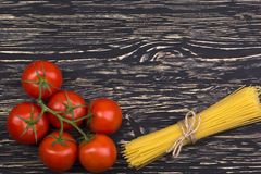 Bunch of spaghetti pasta with fresh tomatoes. Bunch of spaghetti pasta with fresh tomatoes on wooden table Royalty Free Stock Photography