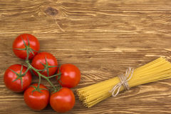 Bunch of spaghetti pasta with fresh tomatoes. Bunch of spaghetti pasta with fresh tomatoes on wooden table Stock Image
