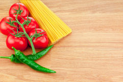 Bunch of spaghetti pasta, green hot peppers and Ripe tomatoes Stock Photos