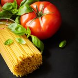 Bunch on spaghetti with tomato and basil. Bunch on spaghetti among tomato with fresh basil against dark background Stock Images