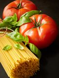 Bunch of spaghetti among tomato with fresh basil. Bunch of raw spaghetti among tomato with fresh basil in close up Stock Images