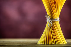 Bunch of spaghetti on wooden table -  purple background Royalty Free Stock Images