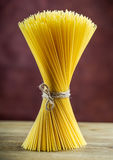 Bunch of spaghetti on wooden table -  purple background Royalty Free Stock Image