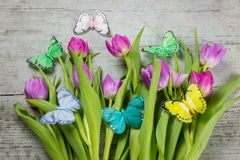 Bunch of spring tulips with colorful butterflies royalty free stock photography