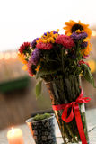 Bunch of summer flowers and a burrning candle on the terrace Royalty Free Stock Photos