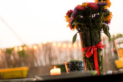 Bunch of summer flowers and a burrning candle on the terrace Royalty Free Stock Photography