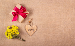 A bunch of summer yellow flowers, a gift box and a wooden heart. Romantic concept. Backgrounds and textures Stock Photography