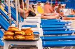 Bunch of sweet donuts lying down on salver on the table on the Paralia beach on Aegean Sea coast in Greece. Paralia, Greece - June 11, 2013: Bunch of sweet royalty free stock images