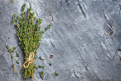 Bunch of Thyme on Dark Slate Top View. Food background with bunch of thyme tied with string. Top view on dark slate Stock Photo