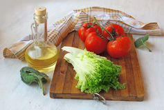 Bunch of tomato and a head of lettuce on the board next to the b Stock Images