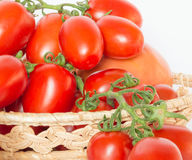 Bunch of tomatoes in a basket with tomato juice Royalty Free Stock Photos