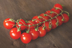 Bunch of tomatoes on a wooden background. A bunch of small red cherry tomatoes on a brown wooden background side Stock Photography