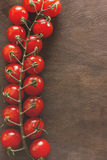 Bunch of tomatoes on a wooden background. A bunch of small red cherry tomatoes on the side of a wooden background. Space for your text Royalty Free Stock Photography