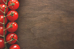 Bunch of tomatoes on a wooden background. A bunch of small red cherry tomatoes on the side of a wooden background. Space for your text Royalty Free Stock Images