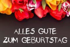 Bunch of tulips with blackboard: happy birthday in German language Stock Photo